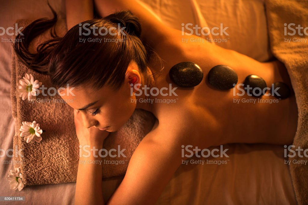 Above view of young woman during lastone therapy at spa. stock photo