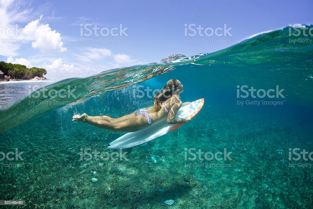 Above/Below duckdive surfer girl stock photo