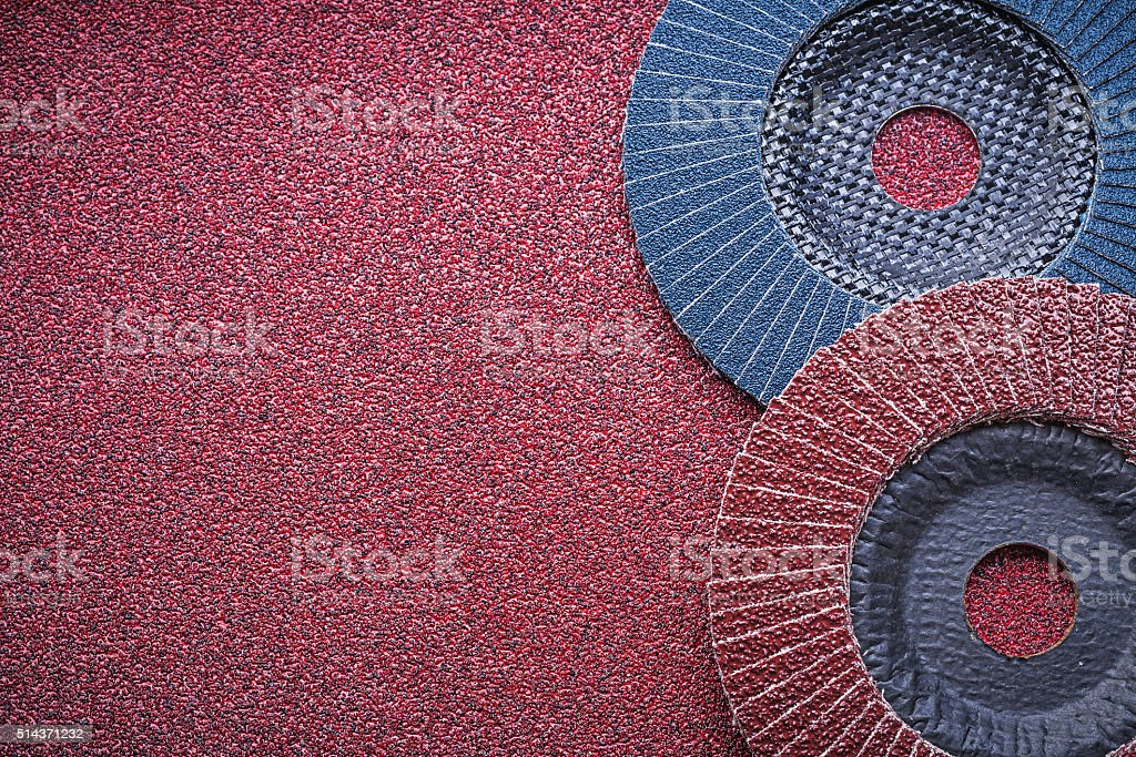 Abrasive flap wheels on emery paper top view stock photo