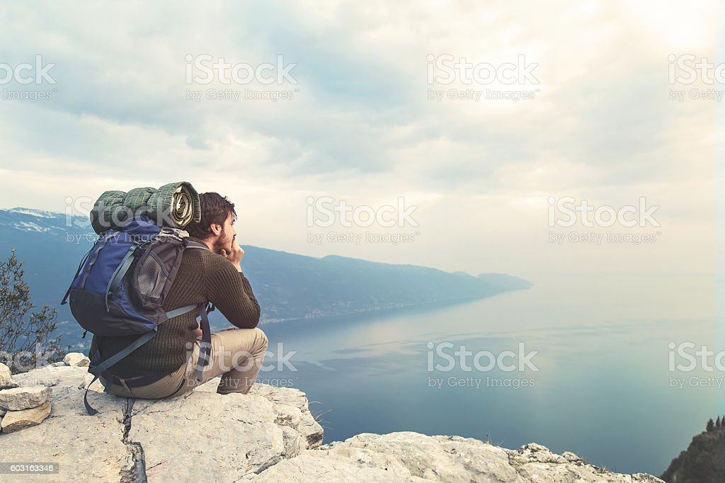 absorbed boy on mountain's top stock photo