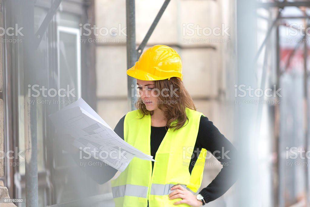 Absorbed female engineer checking office blueprints stock photo