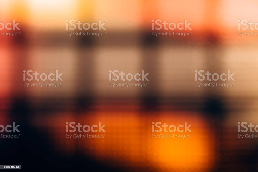 Abstract blurred background of glass block wall. Yellow-red bokeh stock photo