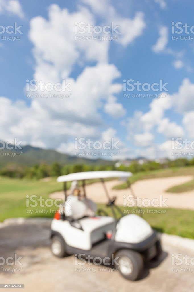 Abstract blurred photo of golf cart and beautiful blue sky background.