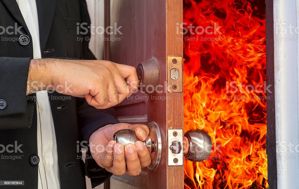 abstract business man will close the door fire burning stock photo