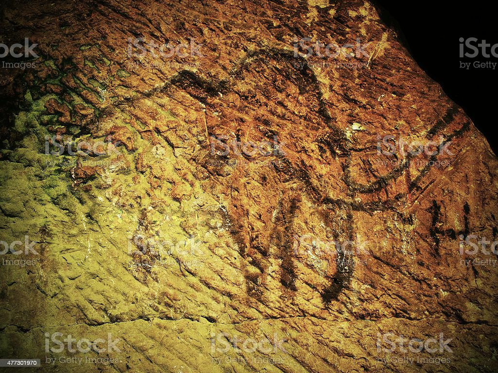 Abstract children art in sandstone cave. Black carbon mammut paint stock photo