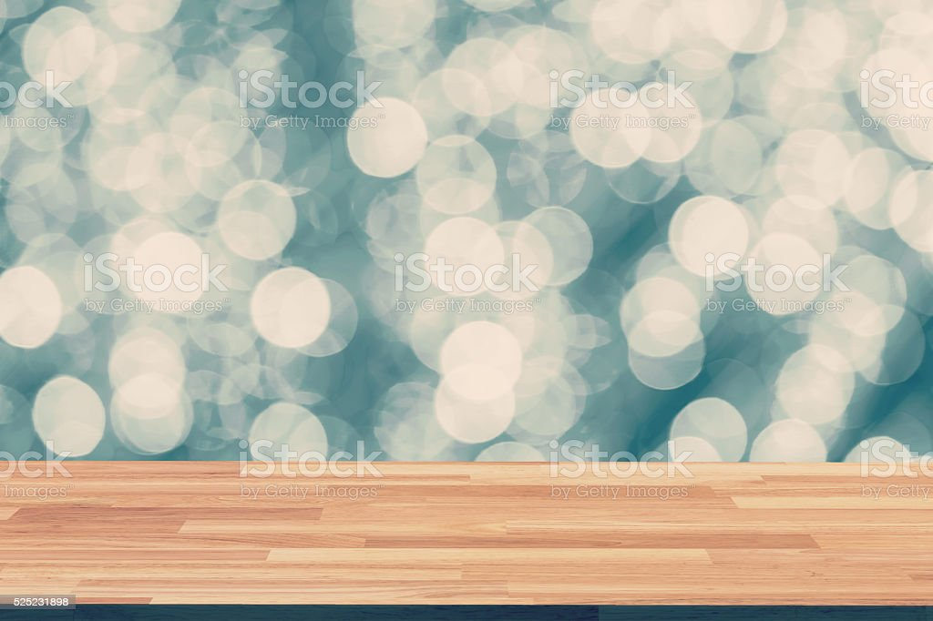 Abstract circular boken night and wood table with space stock photo