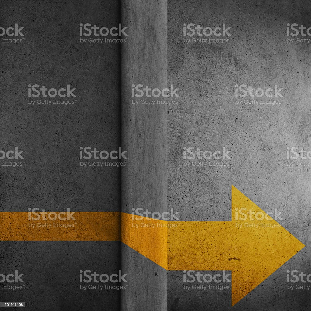Abstract concrete block with yellow arrow sign stock photo
