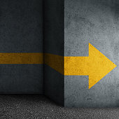Abstract concrete block with yellow arrow sign