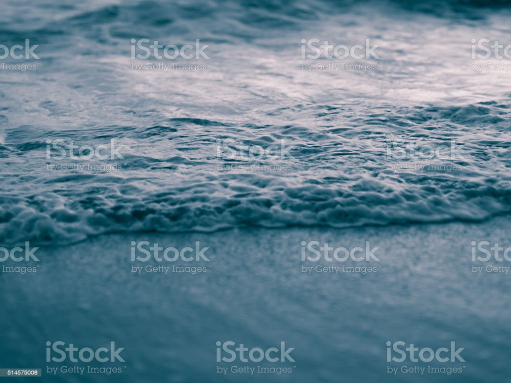 Abstract cool toned image of ocean wave on beach stock photo