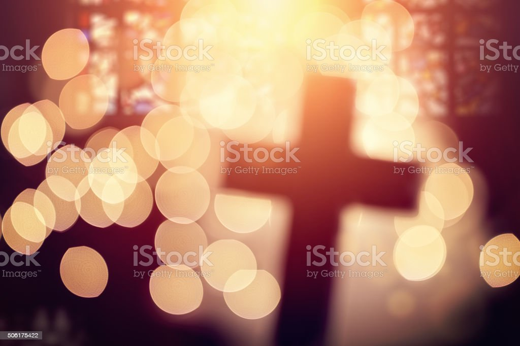 Abstract defocussed cross silhouette in church interior against...