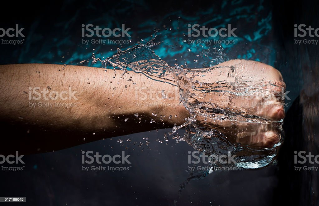 Abstract Fist Punching Into Water stock photo