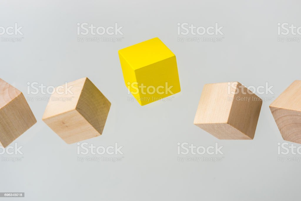 Abstract geometric real floating wooden cube on grey background stock photo