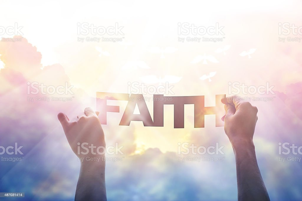 abstract, hand holding a word faith in the colorful sky stock photo