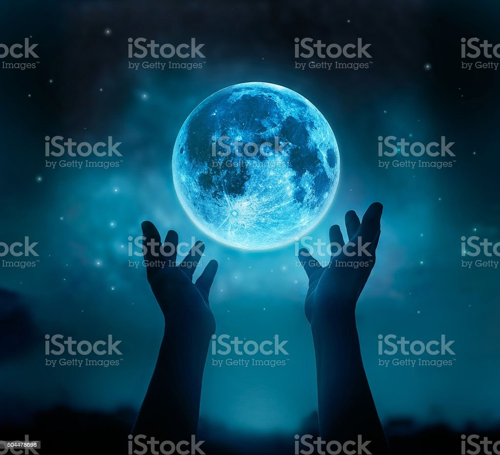 Abstract hands while praying at blue full moon with stars stock photo