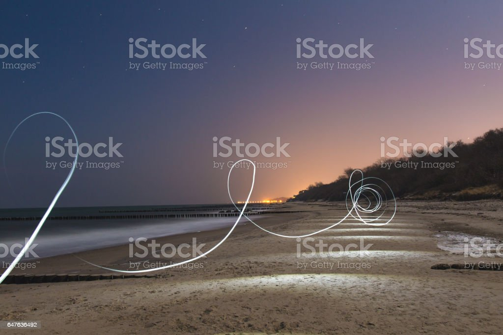 Abstract light trails on beach at night stock photo