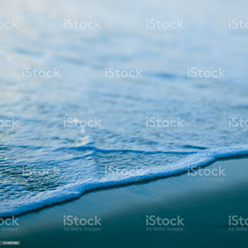 Abstract macro image of small wave on beach stock photo