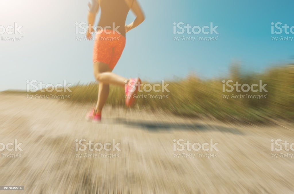 Abstract motion blur:  Young woman jogging cross-country running in summer seaside.  Concept fitness and healthy lifestyle stock photo