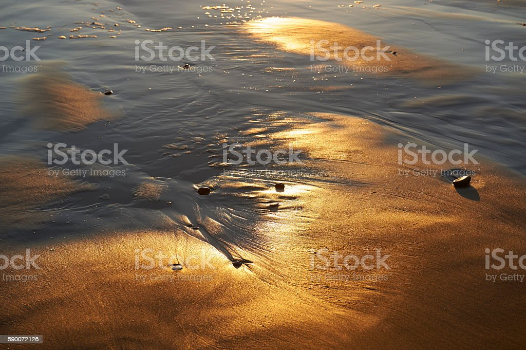 Abstract of sun reflecting off sand at beach stock photo