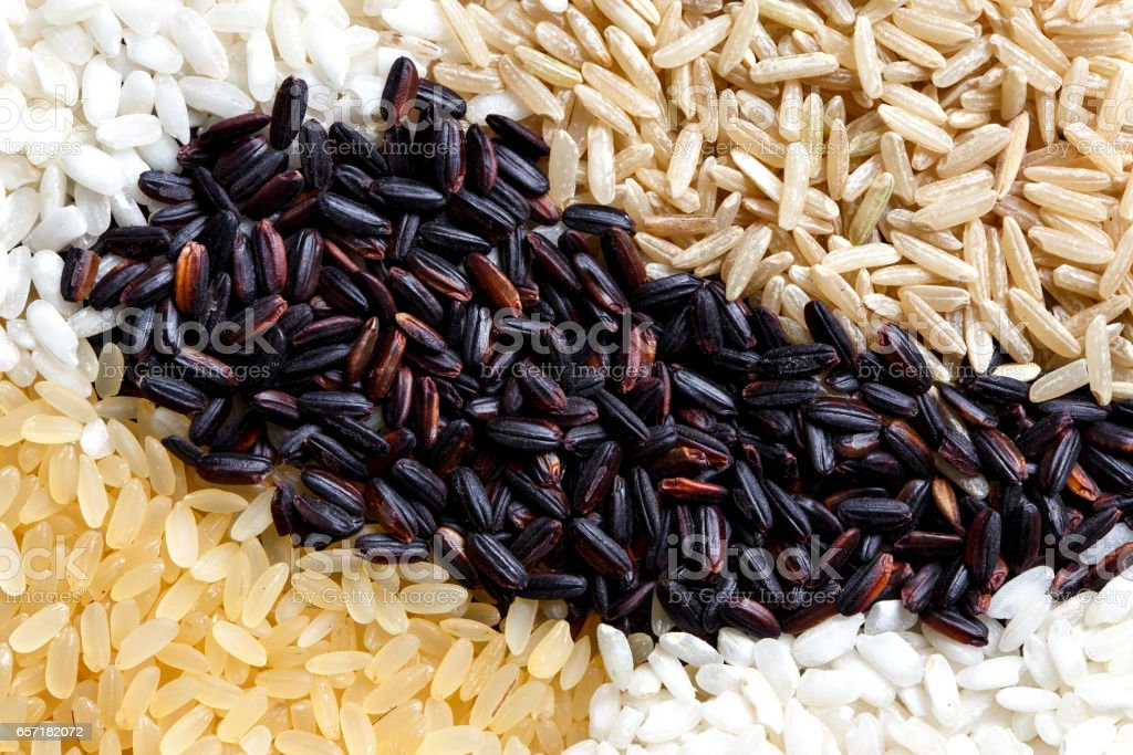 Abstract pattern made of black, white, brown and parboiled rice from above. stock photo