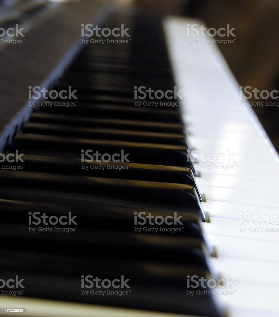 A limited depth of field photograph of a piano keyboard from an...