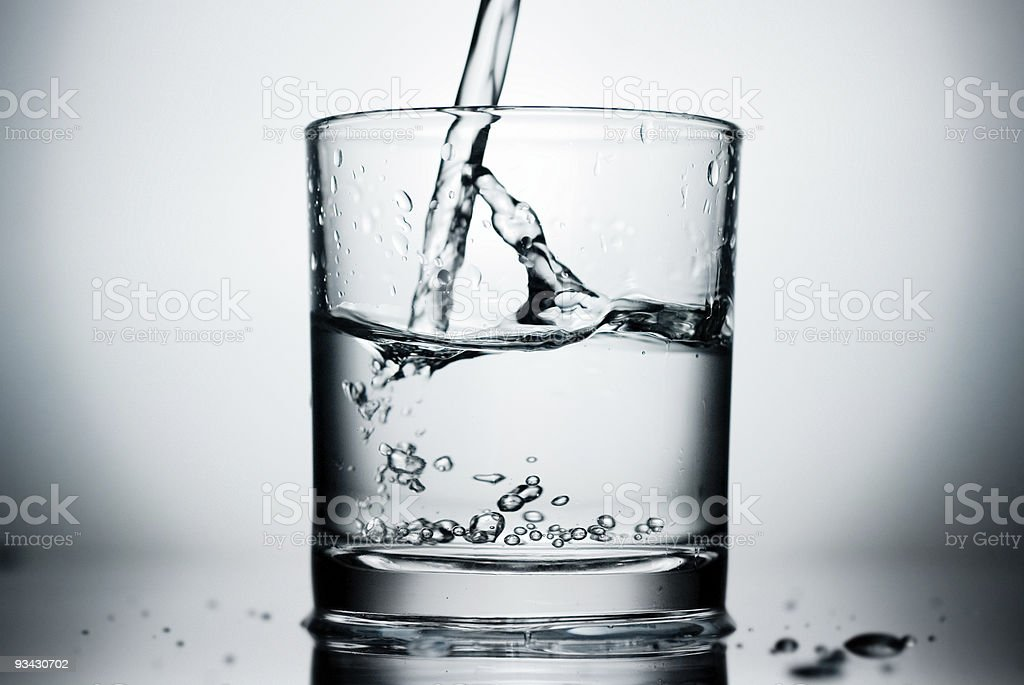 Abstract shot of glass and pouring water splashing stock photo
