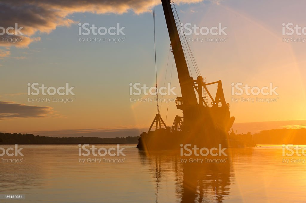 Abstract silhouette of a floating crane at sunrise. stock photo