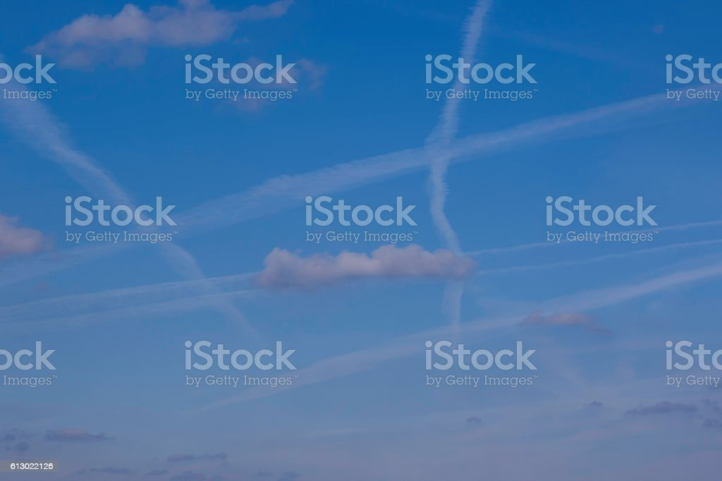 Abstract sky with criss-crossing vapor trails stock photo