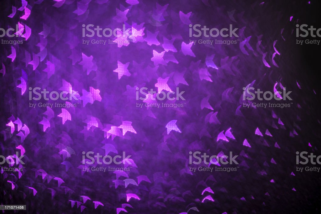 Abstract star shaped bokeh christmas light purple defocussed background stock photo
