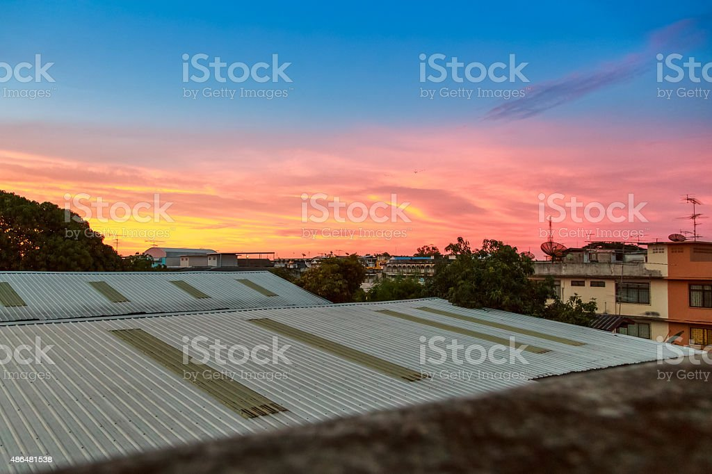 abstract sunrise sky over roof top stock photo