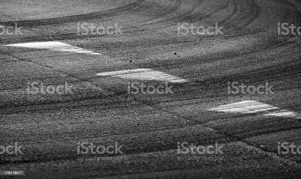 Abstract turning road background with tires track and triangle signs royalty-free stock photo