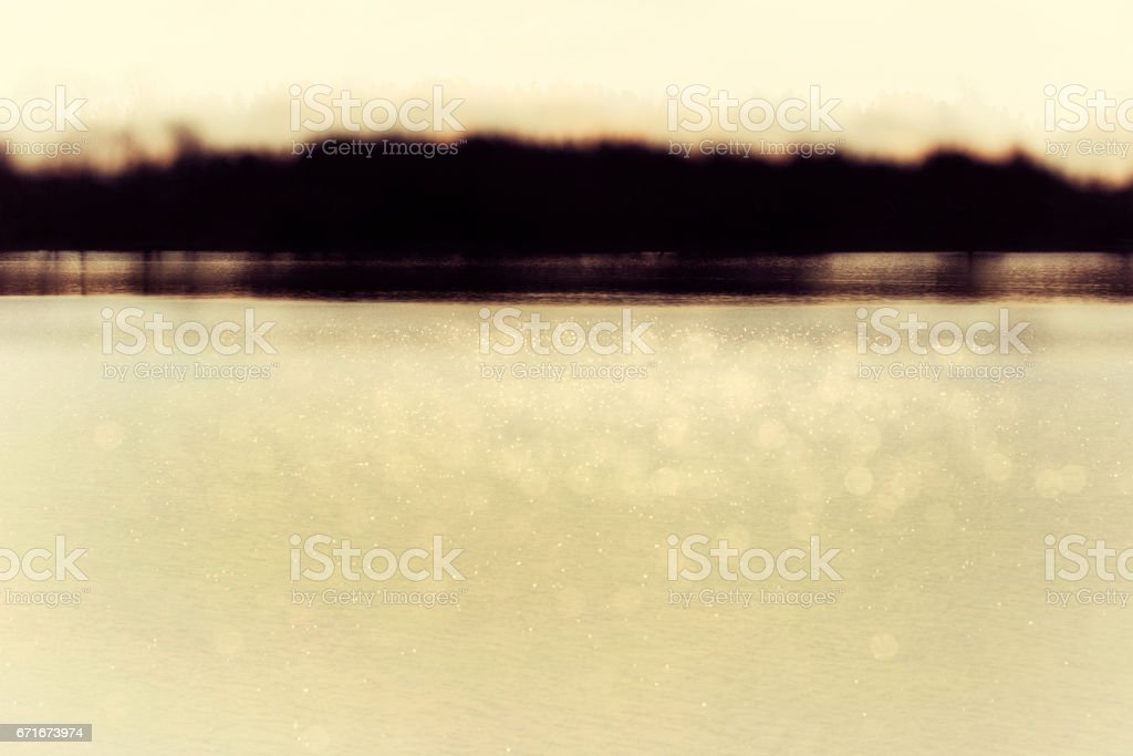Abstract view of a lake with dark brown forest landscape stock photo