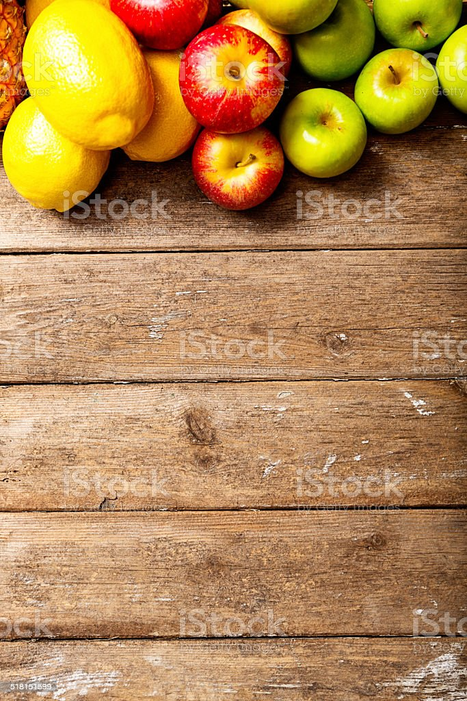 Abundant fresh fruit top border on wooden background stock photo