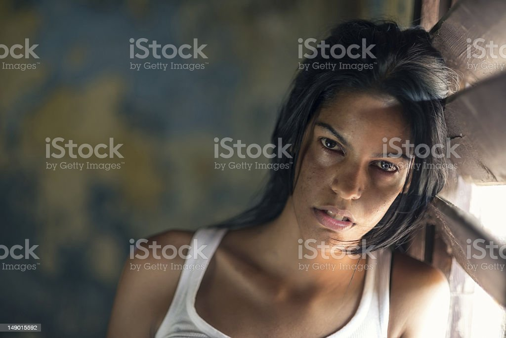 abused and beaten young woman crying at home stock photo