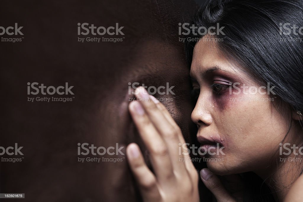Abused woman leaning sadly on wooden wall stock photo