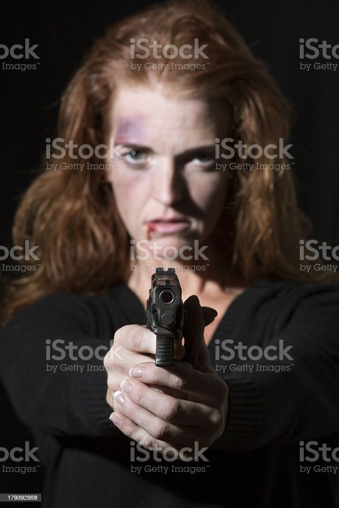 Abused woman with bruises pointing a gun at the camera royalty-free stock photo
