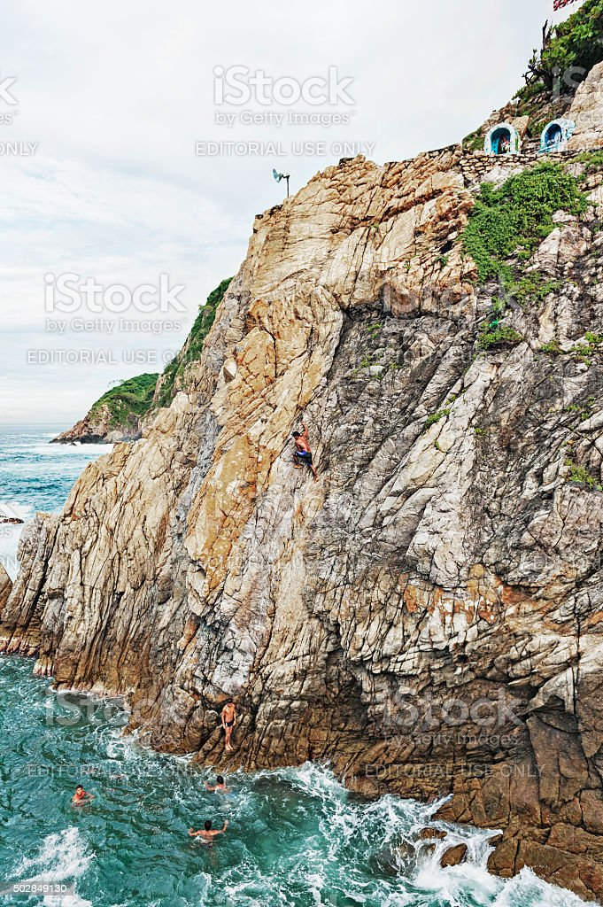 Acapulco Cliff Divers climbing Rocky Cliff and in Water stock photo