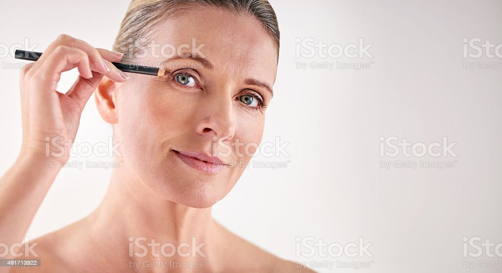Accentuating her eyes with some eyeliner stock photo