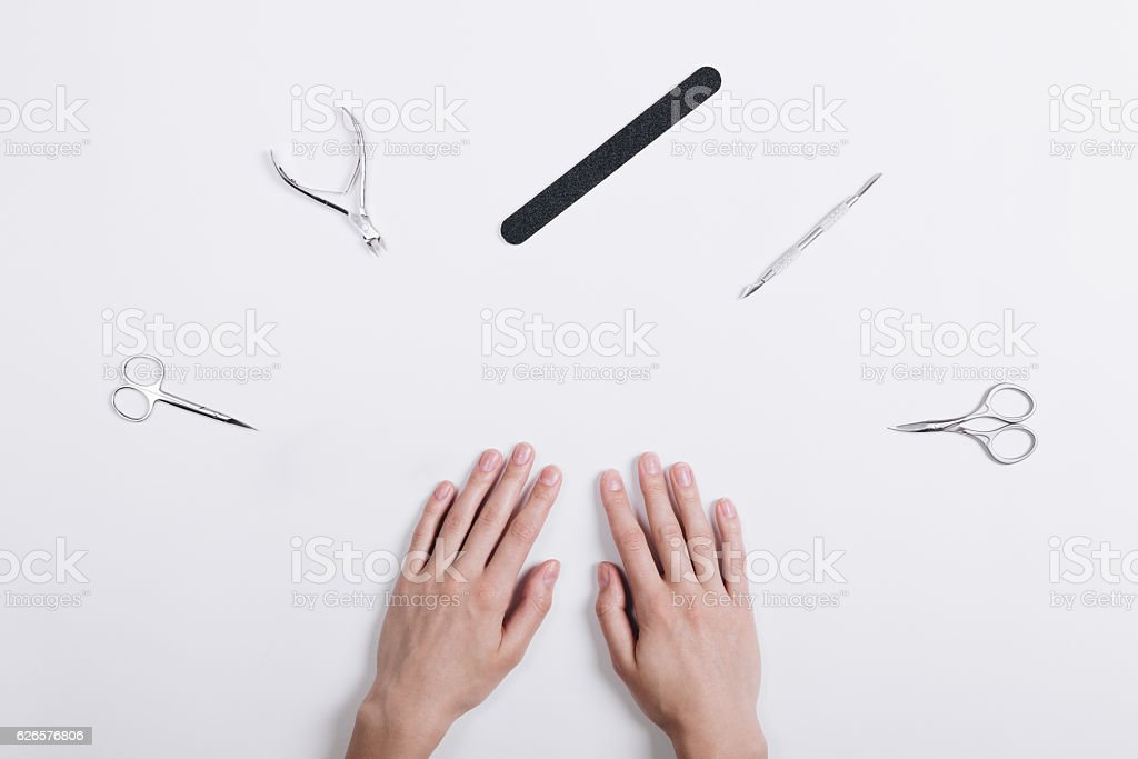 Accessories for manicure lie around a female hands stock photo