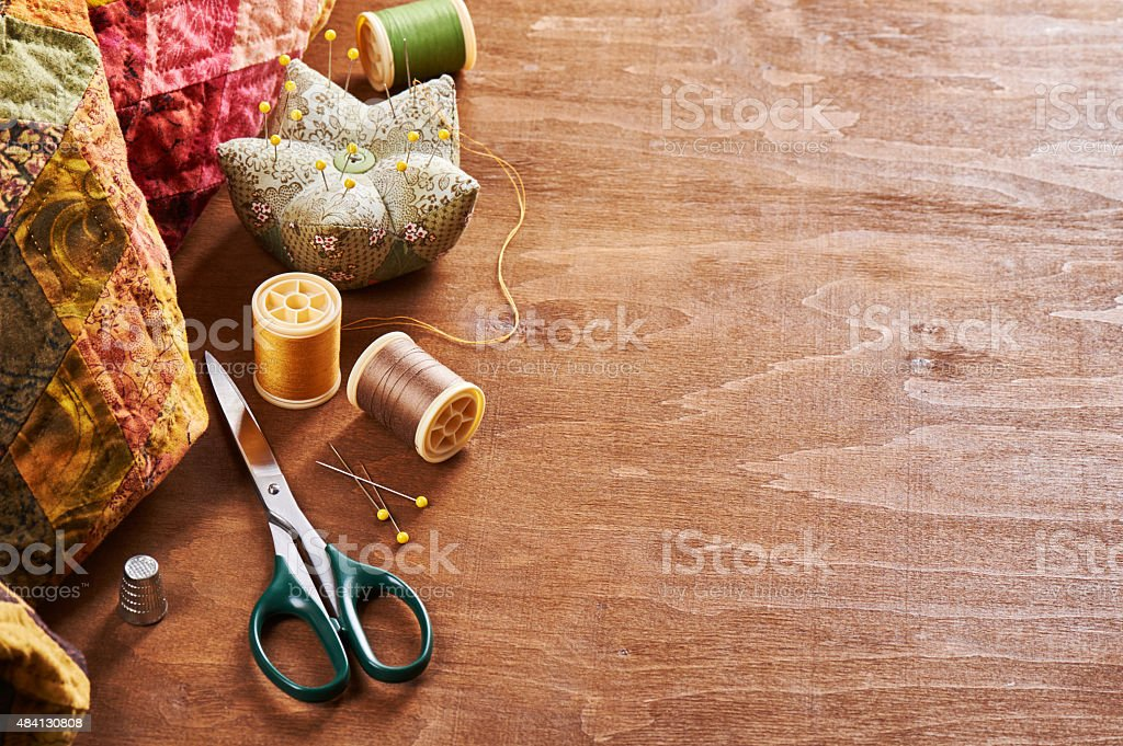 Accessories for patchwork on a quilt on a wood background stock photo