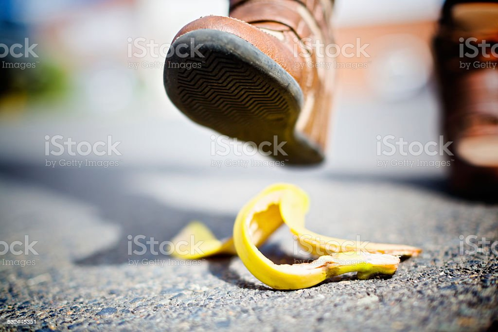 Accident on the way! Booted foot approaching banana skin. stock photo