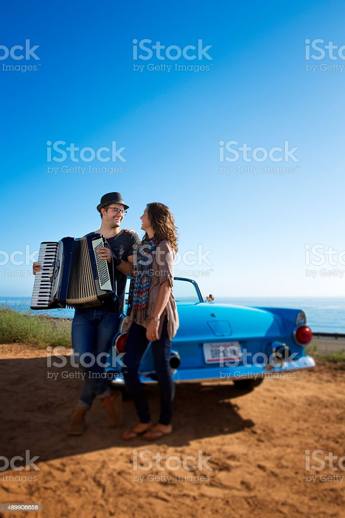 Accordian Couple Laughing by a Blue Convertible stock photo