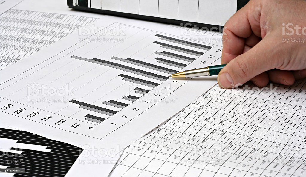 Accountant analyzing a graph and data using a pen stock photo