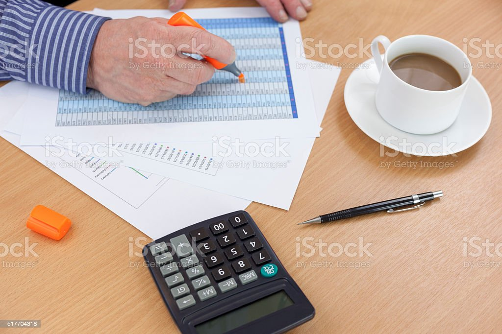 Accountant busy at his desk using an orange highlighter stock photo