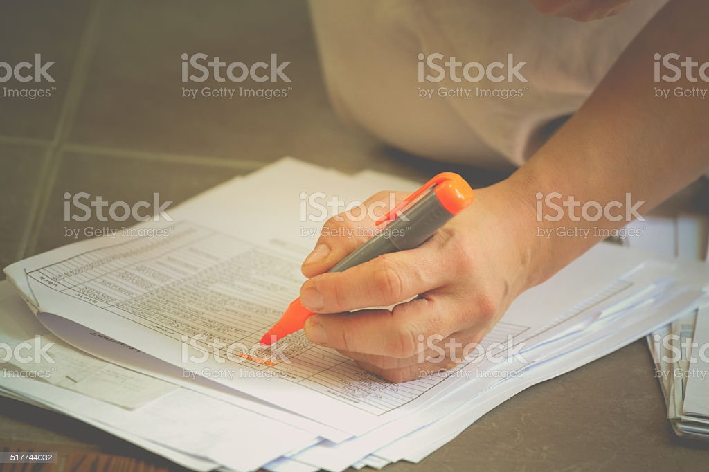 accounting concept : Hand highlighters important number on docum stock photo