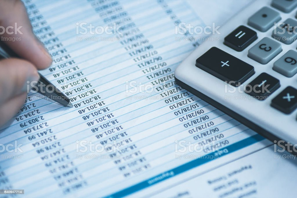 Accounting financial banking stock spreadsheet data with human hand holding pen and calculator in blue. stock photo