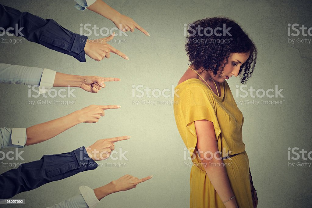 Accusation. Sad woman looking down fingers pointing at her stock photo
