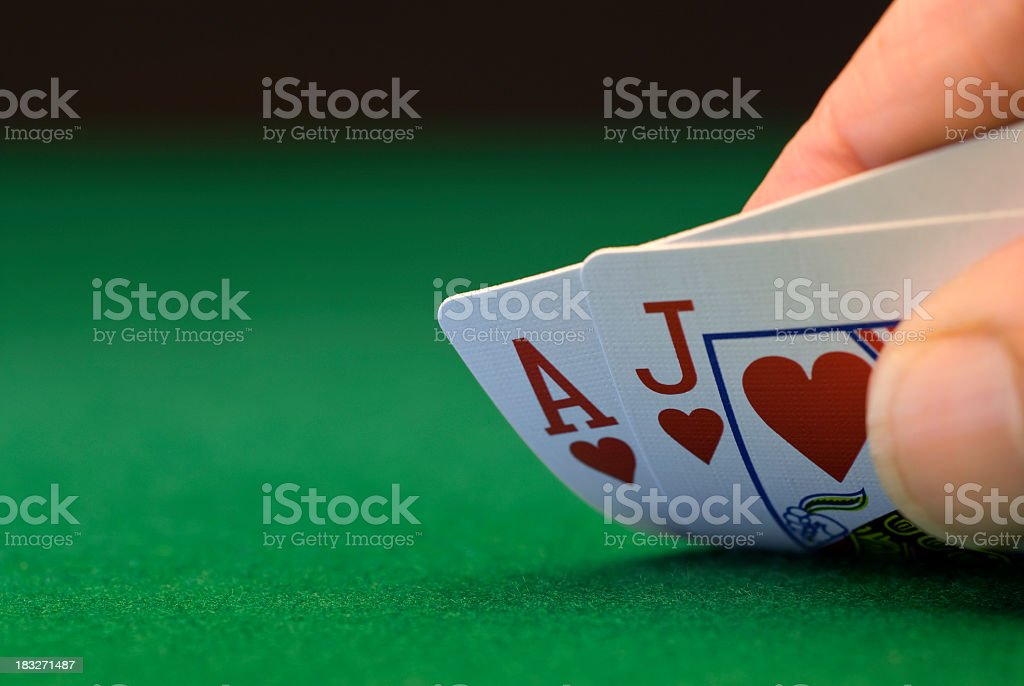 Ace and Jack of hearts on green baize stock photo