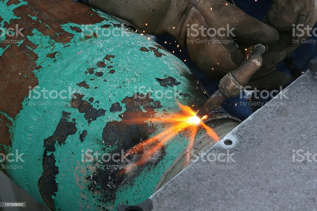 Acetylene torch cutting green pipe bright fire flame glove stock photo