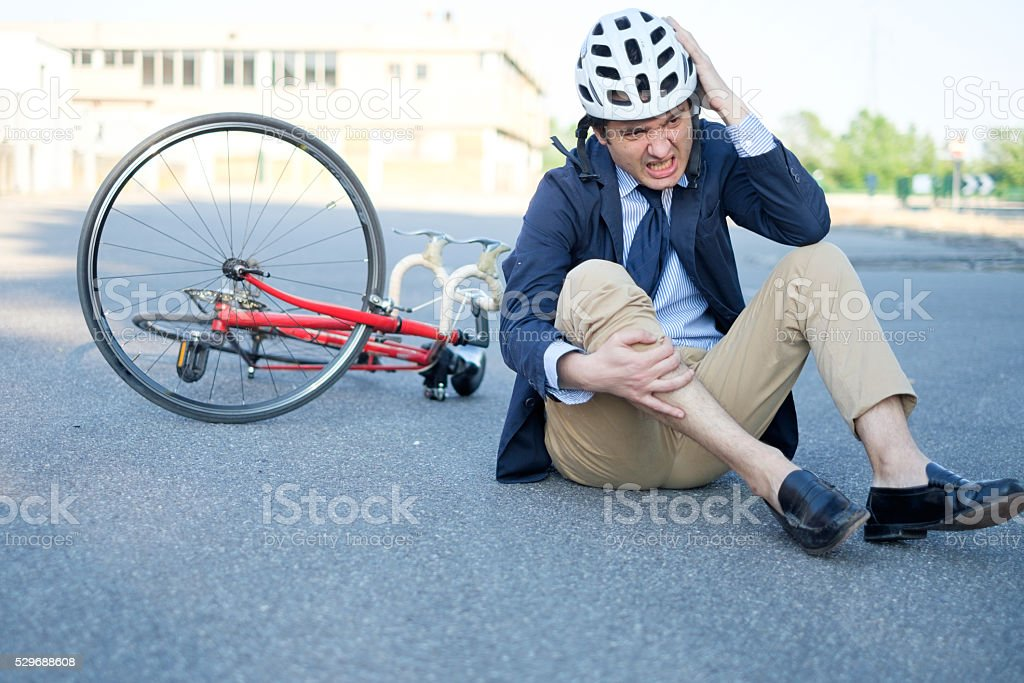 aching man after bicycle accident stock photo