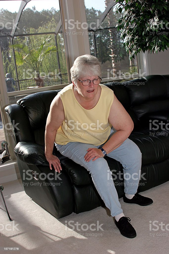 Achy woman on couch at home holding her knee in pain stock photo